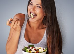 Healthy Women eating salad on a light grey background