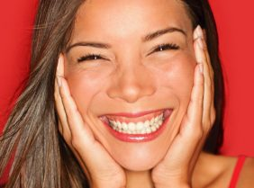 A red background with a lady showing of her clear skin to promote acne scar removal at Pulse Light Clinic